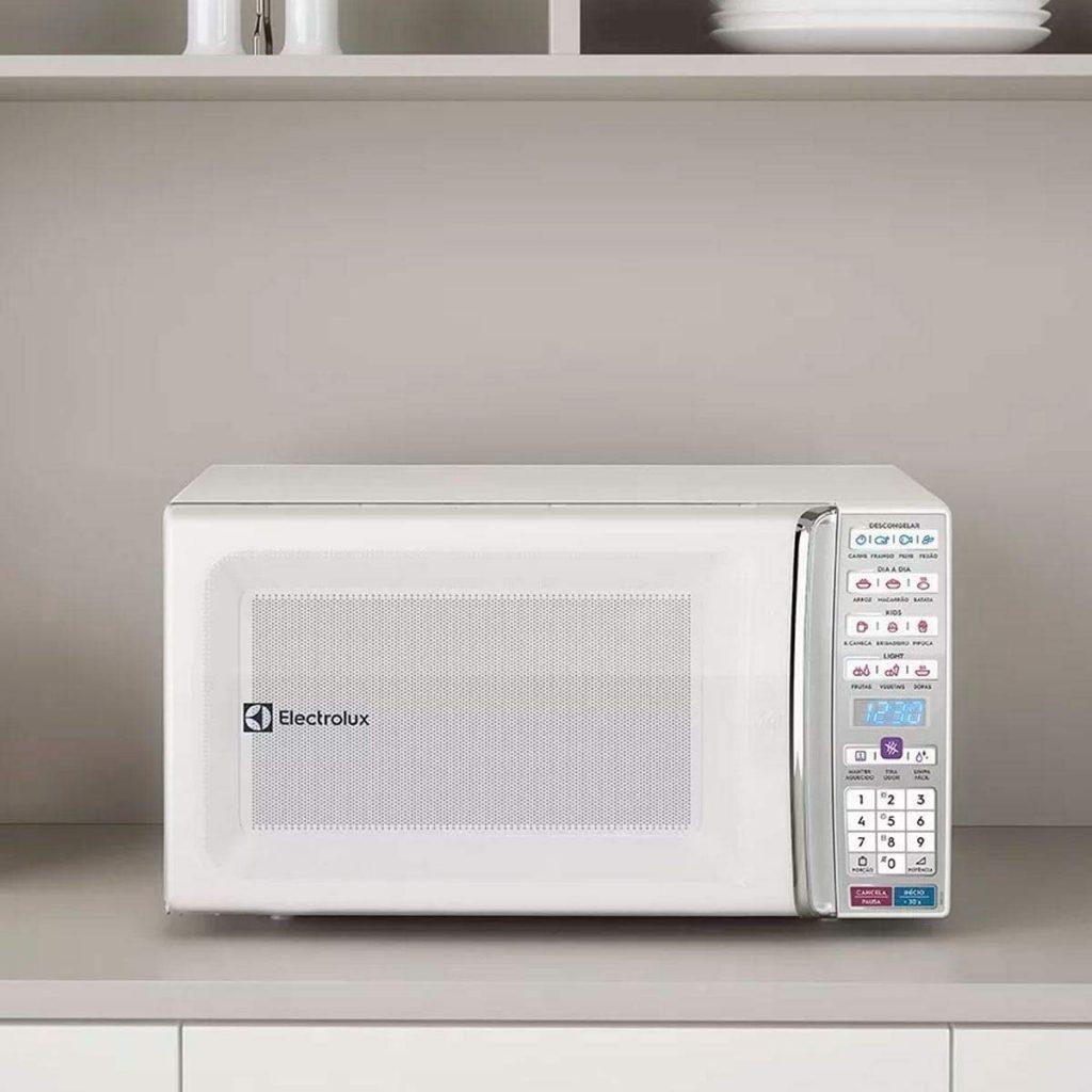 Imagem mostra micro-ondas Electrolux branco em bancada de cozinha.