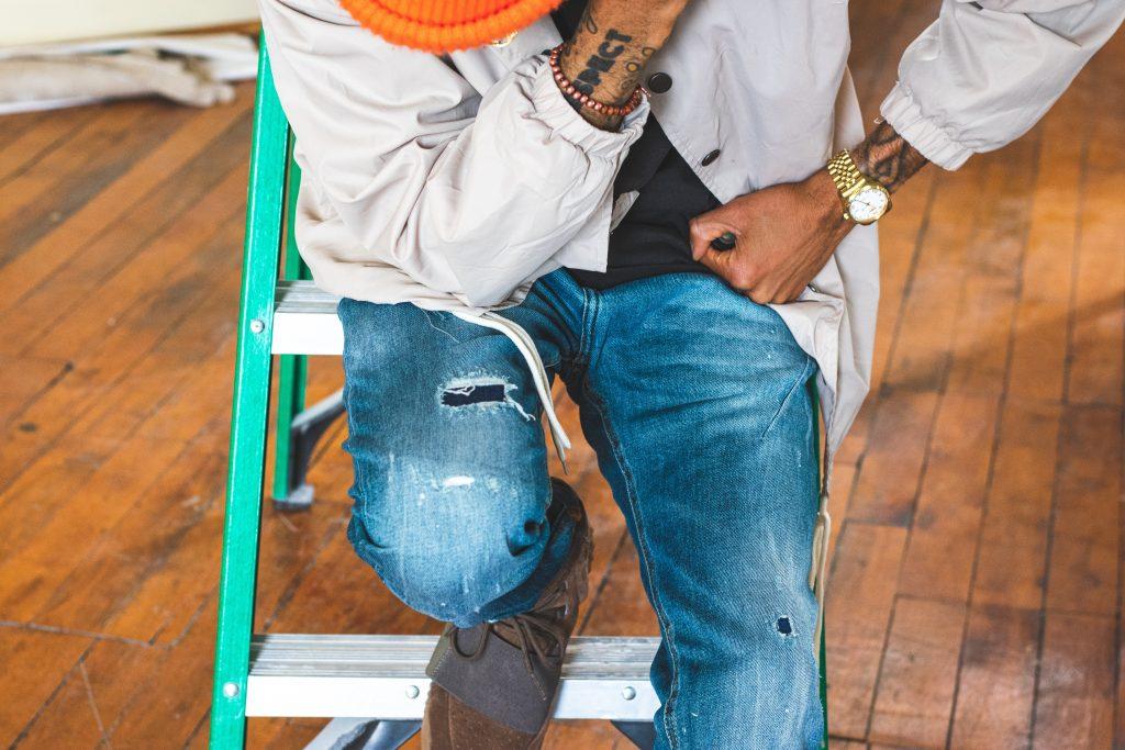 Imagem mostra um homem sentado nos degraus de uma escada doméstica.