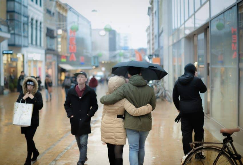 Imagem de um casal andando na rua usando um guarda-chuva.