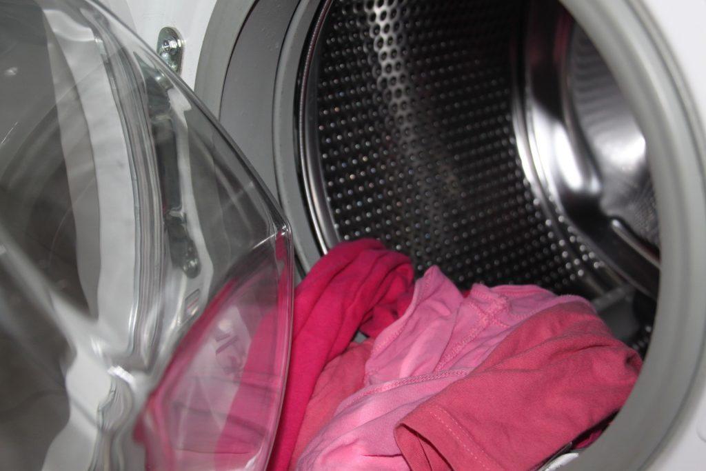 Detalhe de máquina de lavar com tampa aberta e roupas.