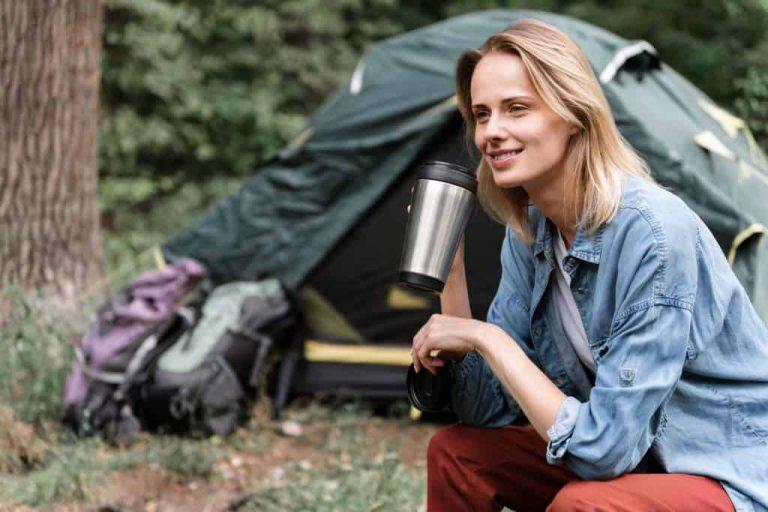 Na foto uma mulher sentada em um acampamento com uma barraca ao fundo segurando um copo térmico.