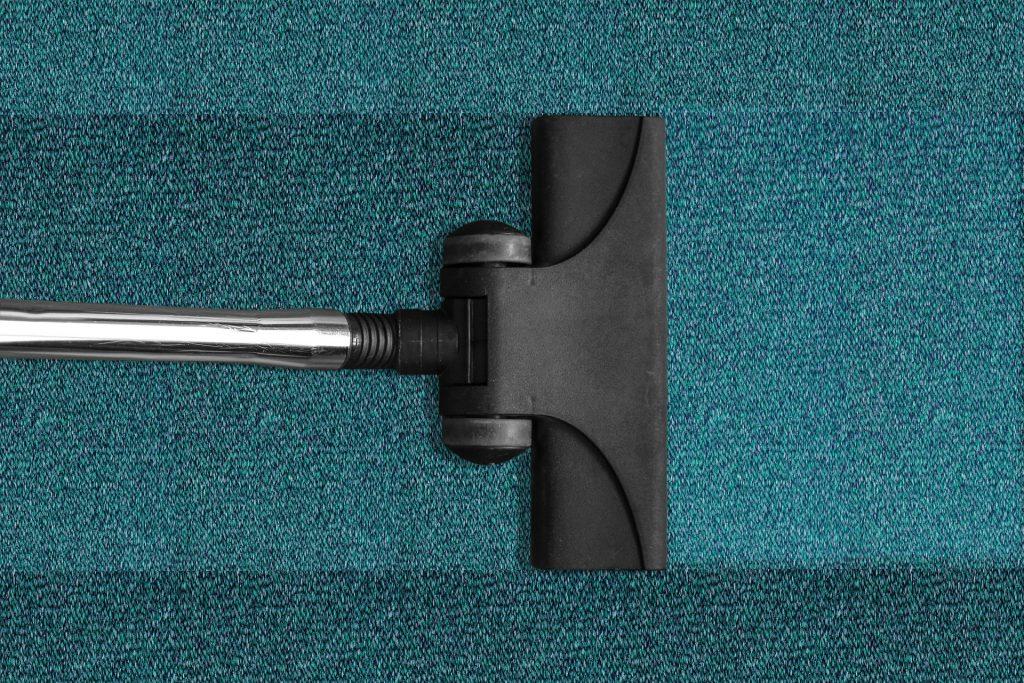 Imagem de bocal de aspirador de pó sendo passado em um tapete verde