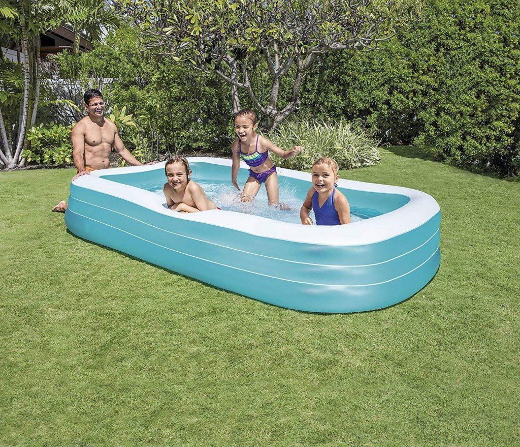Homem agachado ao lado da piscina inflável enquanto três crianças brincam em seu interior.