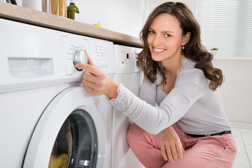 Mulher ligando máquina de lavar roupa. Link: