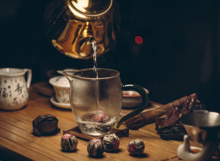 Imagem de pessoa preparando uma infusão com jogo de chá oriental