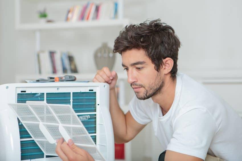 Homem mexendo em filtro de ar condicionado portátil