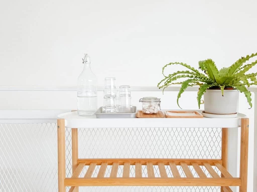 Imagem de bancada de madeira com jogo de copos, jarra de vidro e vaso autoirrigável branco com compartimento oculto.