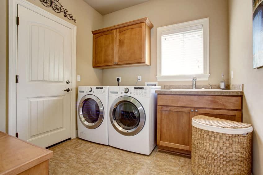 Imagem de lavanderia com armários, máquina de lavar roupa e secar.