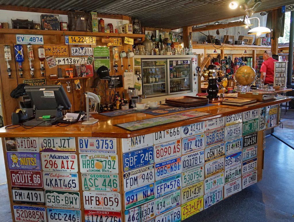 Imagem de bar repleto de placas decorativas imitando placas de carro.