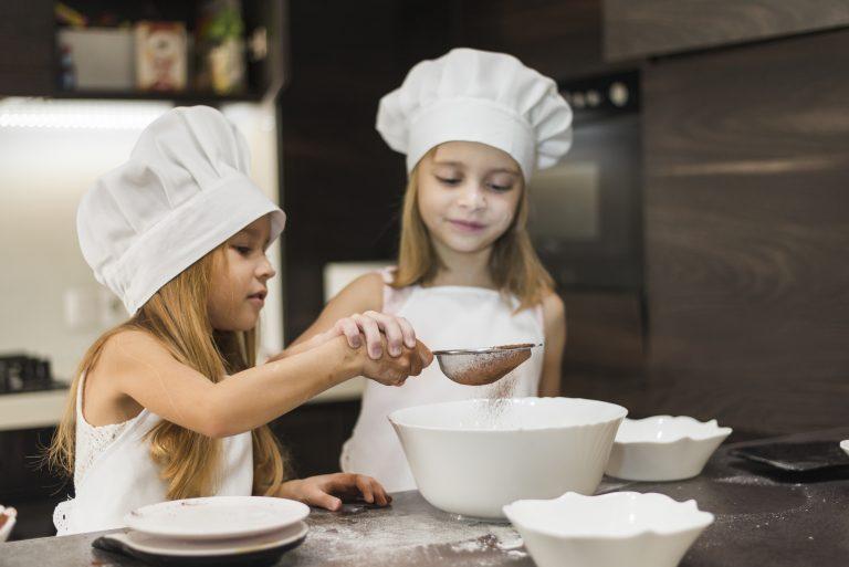 duas meninas usam peneira para dispor cacau em pó em tigela no preparo de receita