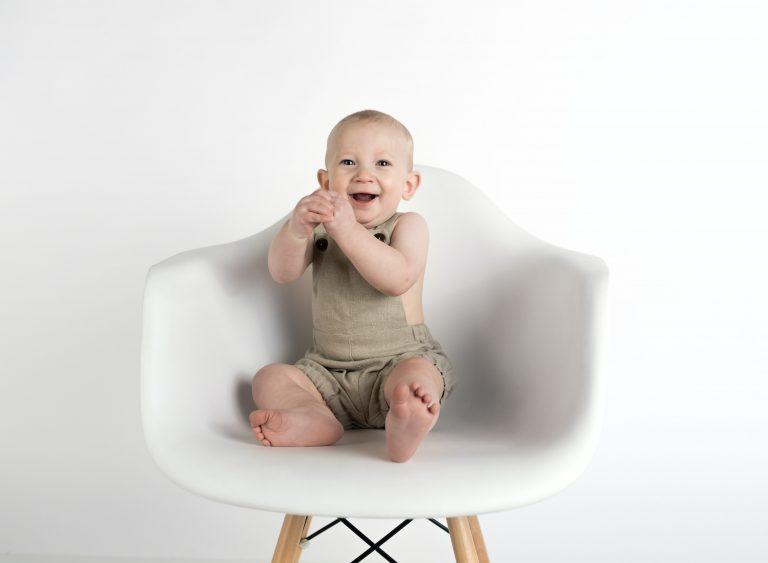 Foto de um bebê sorridente, sentado em uma cadeira branca, com pés de madeira, em uma parede branca.