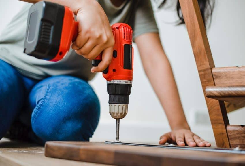 Na foto é possível ver o braço, as mãos e as pernas de uma mulher utilizando uma parafusadeira elétrica em uma tábua de madeira.