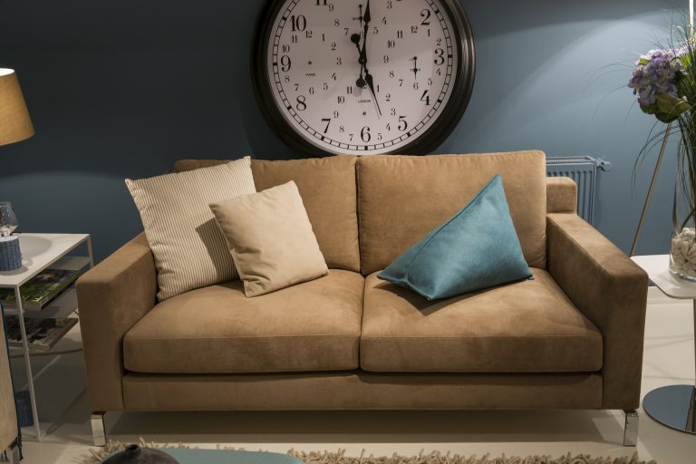 Imagem de sofá de dois lugares com almofadas e relógio ao fundo