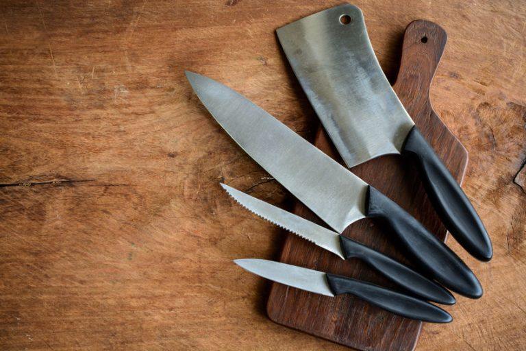 Cutelo junto a conjunto de facas sobre tábua de corte