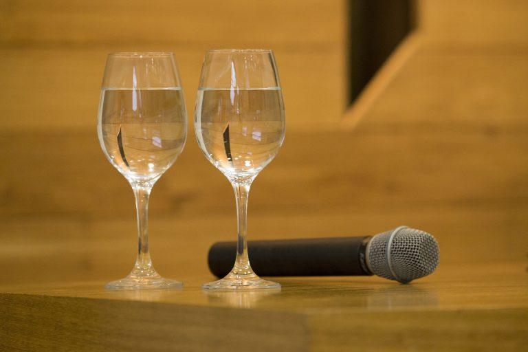 Taças de água simples sobre mesa e ao lado de microfone