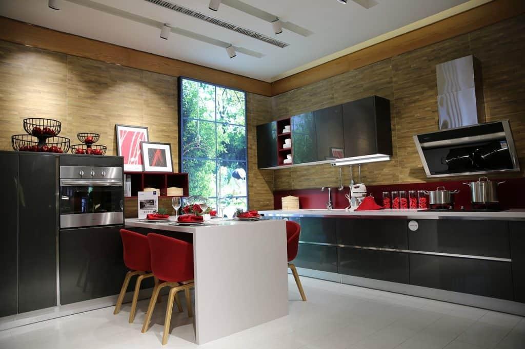 Imagem de cozinha moderna com coifa de parede sobre fogão embutido.