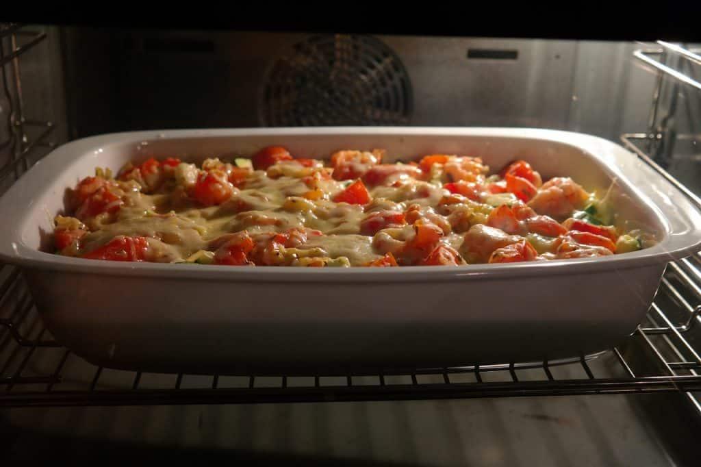 Imagem de travessa no forno com legumes e queijo.