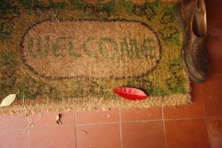 Imagem de sapato masculino ao lado de capacho com mensagem de boas-vindas