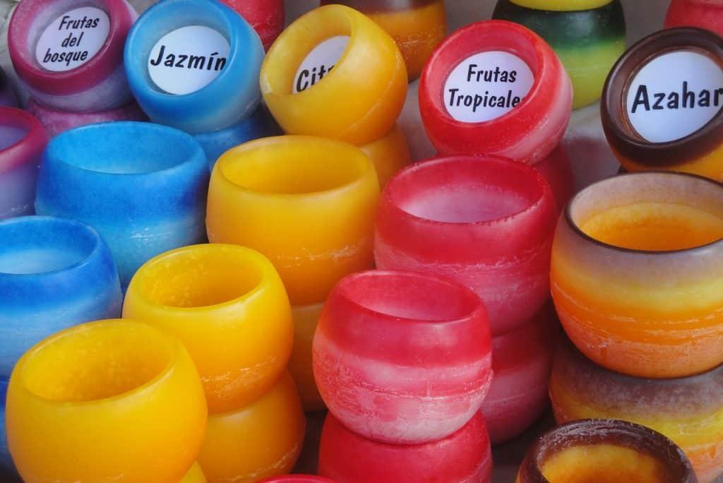 Imagem com várias velas coloridas e com etiquetas informando o aroma de algumas.