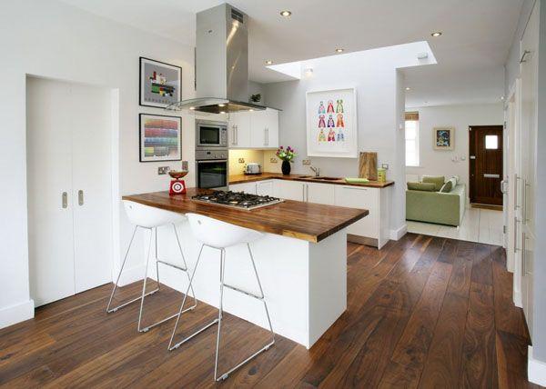 Foto de uma cozinha com aspecto clean, no estila americana, com diversos armários, um paneleiro ao lado de uma geladeira, fogão, bancada e bancos.