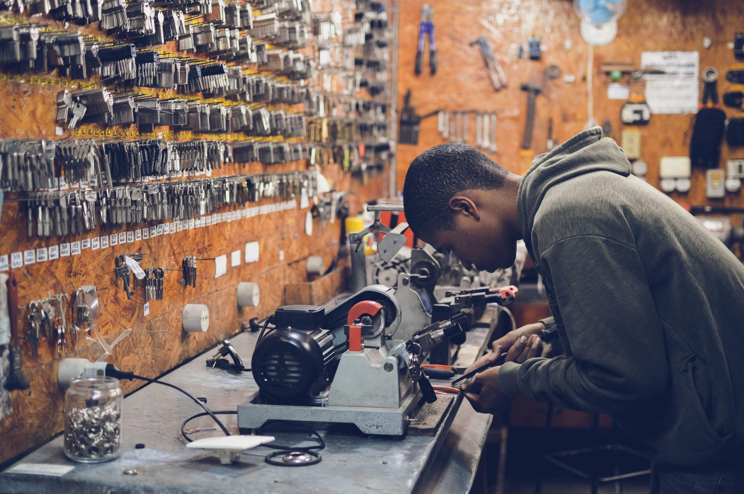 Imagem mostra um chaveiro fazendo a copia de uma chave. Ele está de cabeça baixa, em frente à uma máquina e uma parede repleta de chaves. Ao fundo, sua oficina.