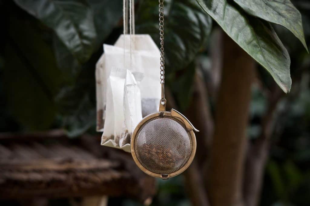 Imagem de infusor de chá metálico e de infusores de pano pendurados em árvore.