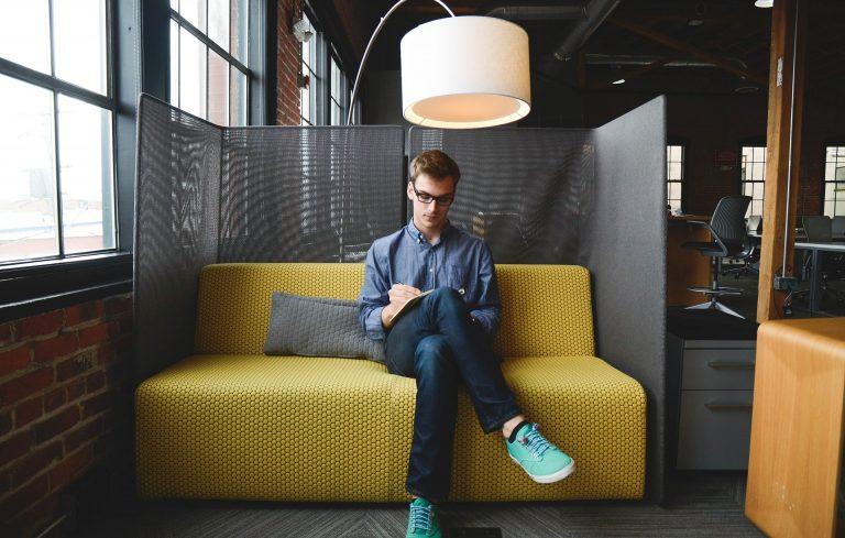 Imagem de homem sentado em sofá de dois lugares amarelo