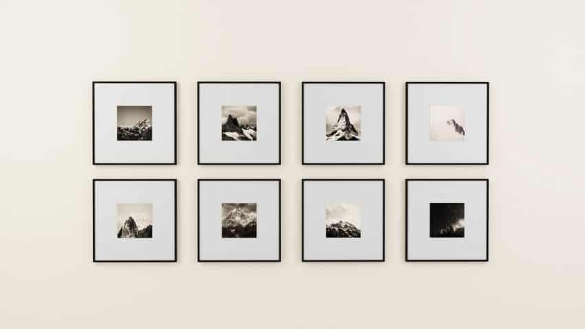 Foto de oito quadros pequenos, todos em preto e branco, com margem branca. Eles exibem imagens de montanhas, em uma parede clara.