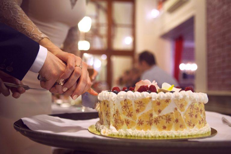 Imagem de casal cortando um bolo de casamento com frutas vermelhas