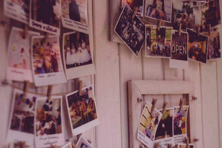 Na foto uma parede de madeira com diversos varais de fotos.