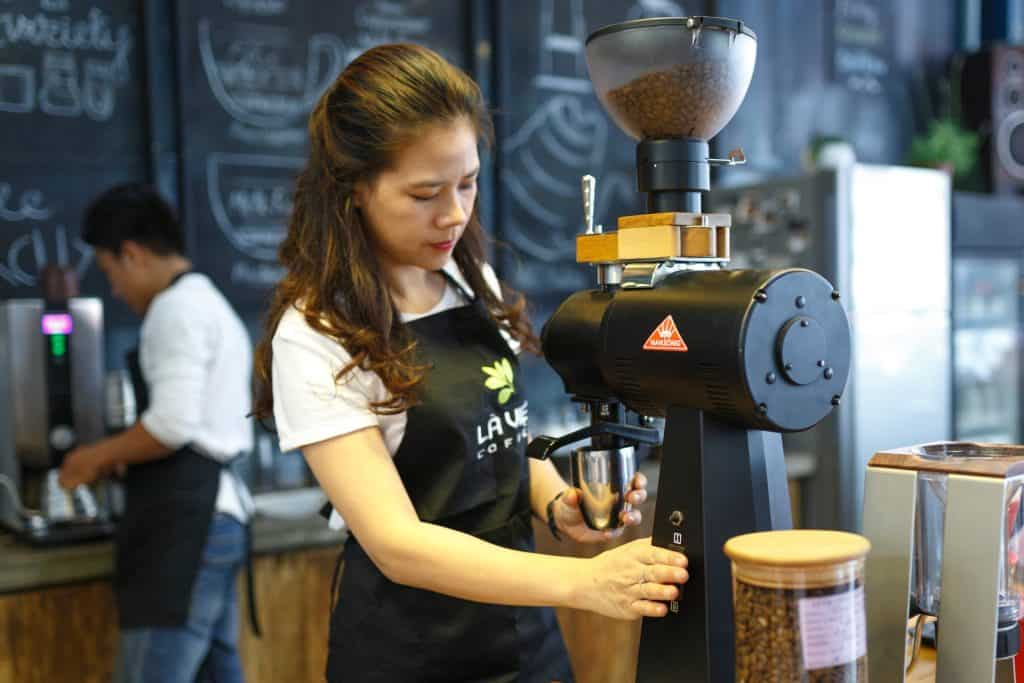 Imagem mostra barista preparando café em cafeteira.