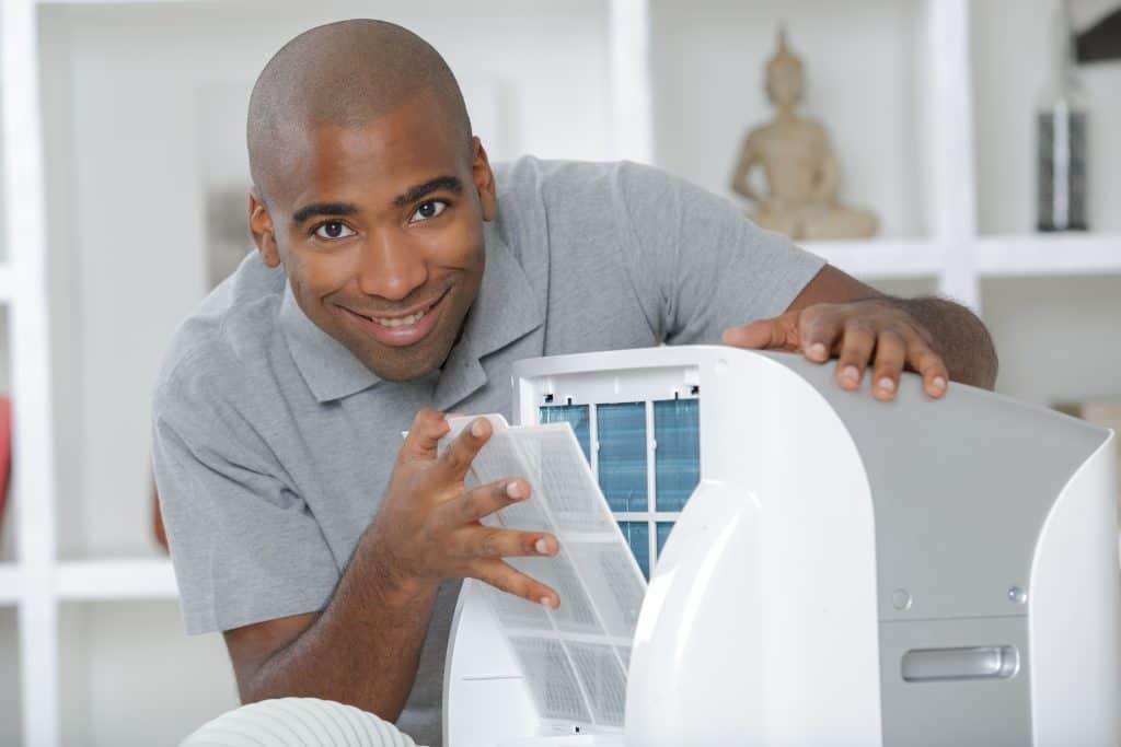 homem sorrindo e mexendo em ar condicionado portátil