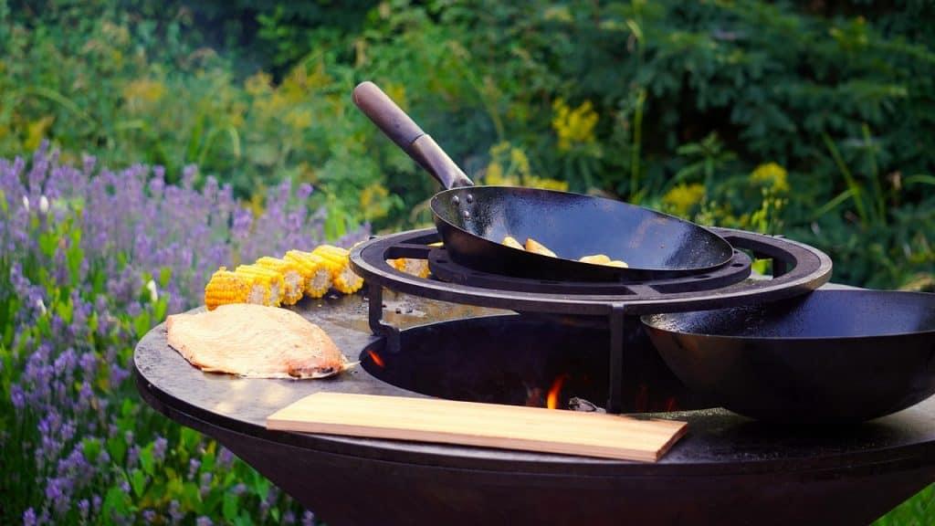 Imagem mostra uma mesa com utensílios como tábua de madeira e frigideira e alimentos como carne e milho.