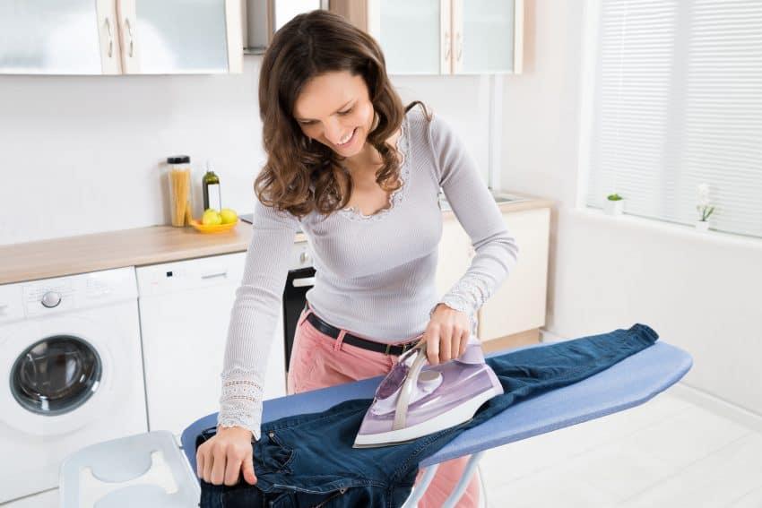 Mulher sorrindo passando roupa na cozinha.