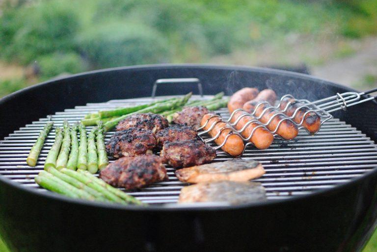 Churrasqueira a carvão preparando peixe, hamburgueres, legumes e linguiça na grelha