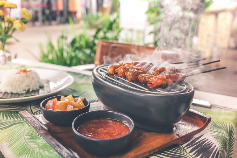 Imagem de mini grill e acompanhamento apoiados em descanso de madeira