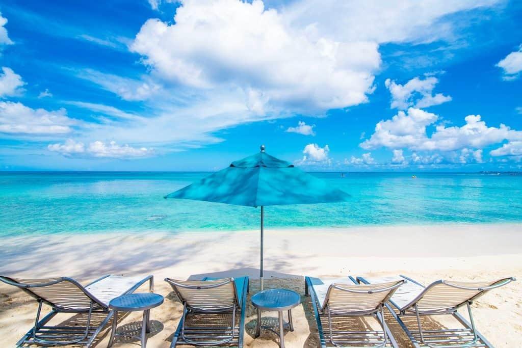 Espreguiçadeiras na beira de um mar paradisíaco.