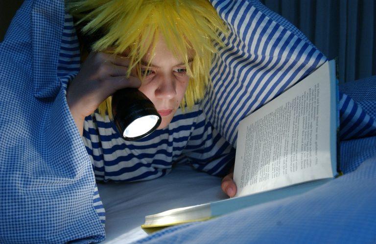 Imagem de pessoa deitada embaixo de edredom queen azul lendo com ajuda de lanterna