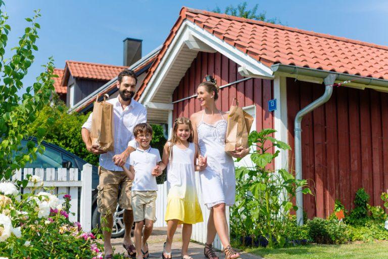 Família entrando em jardim da sua casa com sacolas de papel.