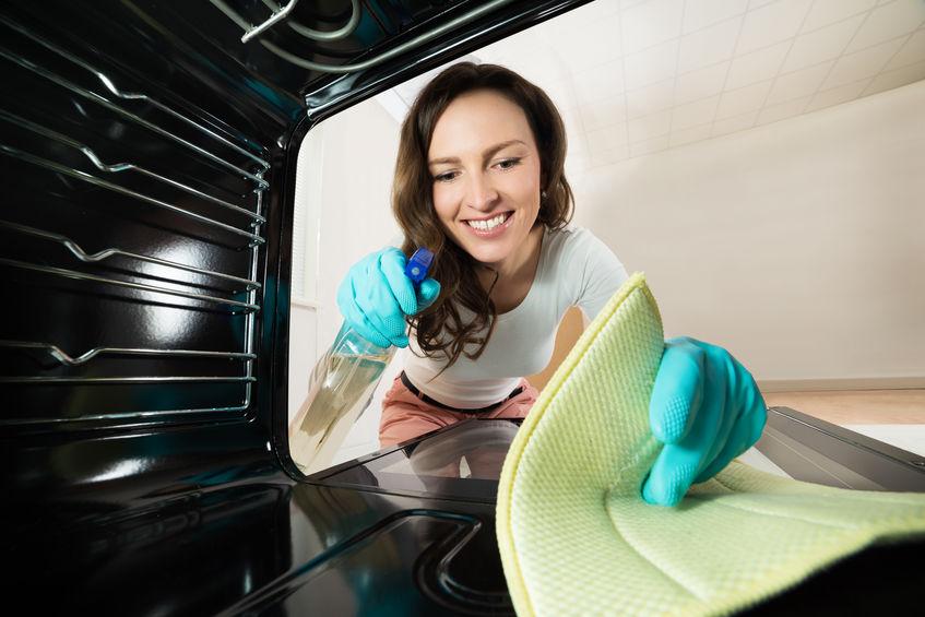 Mulher limpando o forno de um fogão.
