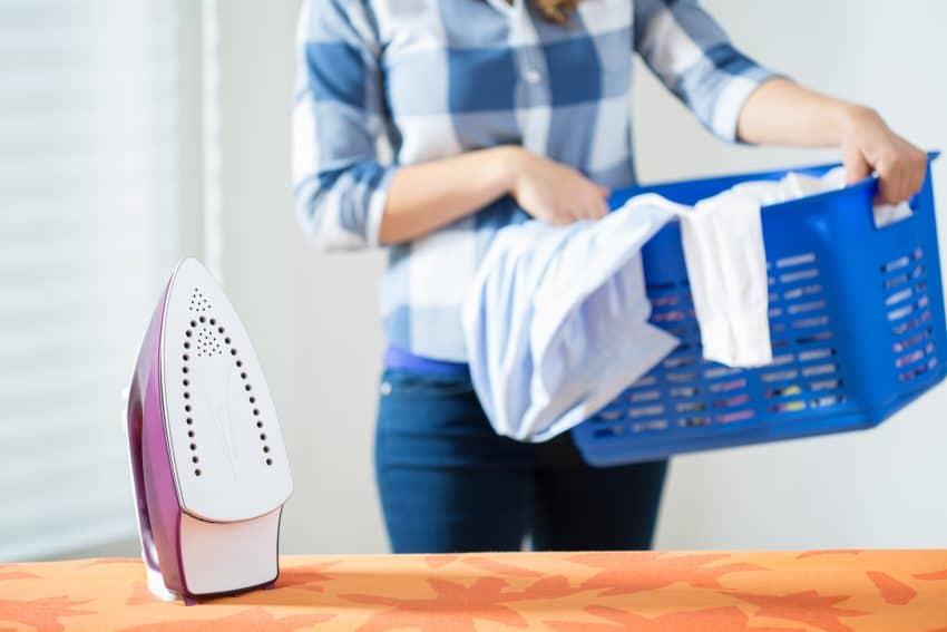 foto de um ferro de passar em pé sobre uma tábua com uma mulher segurando uma cesta de roupas no fundo