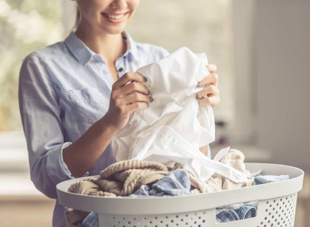 Imagem de mulher segurando roupa perto do cesto de roupas cheio.