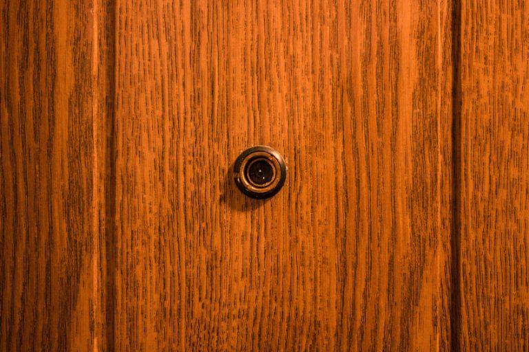 Foto de um olho mágico, em uma porta marrom.