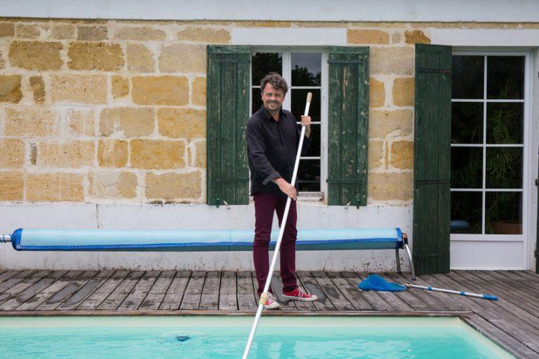 Homem sorri para foto enquanto limpa a piscina, com capa recolhida ao fundo