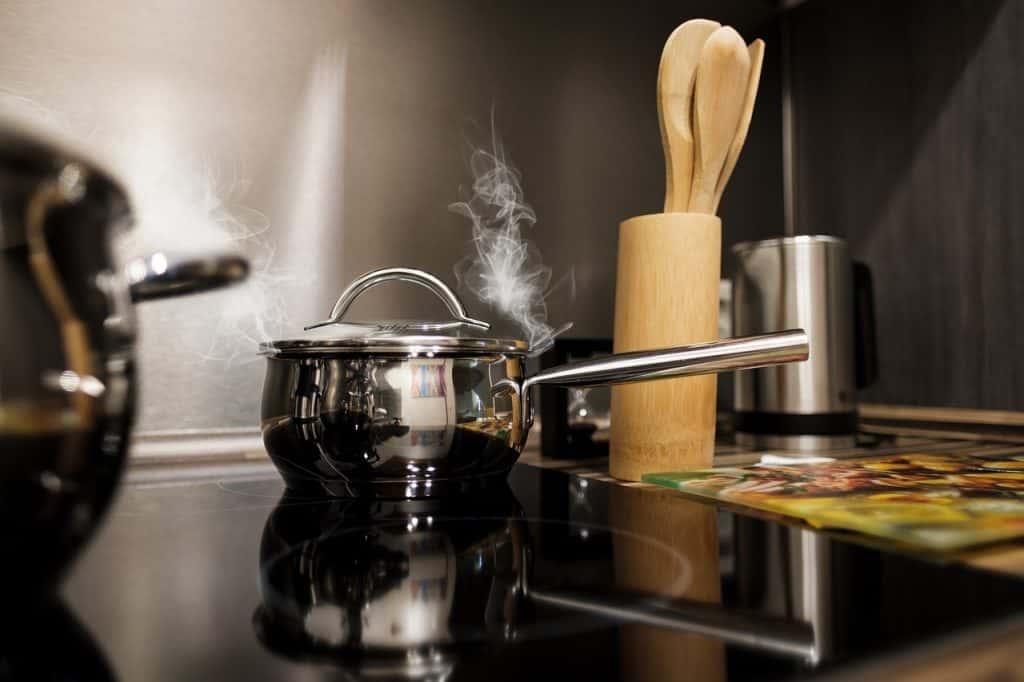 Panelas cozinhando sobre cooktop.