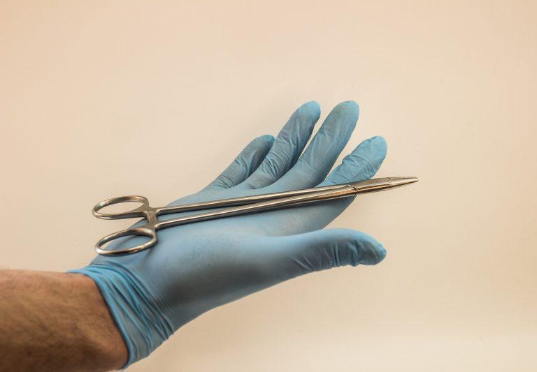 Imagem de médico utilizando luxa de látex para segurar uma tesoura cirúrgica