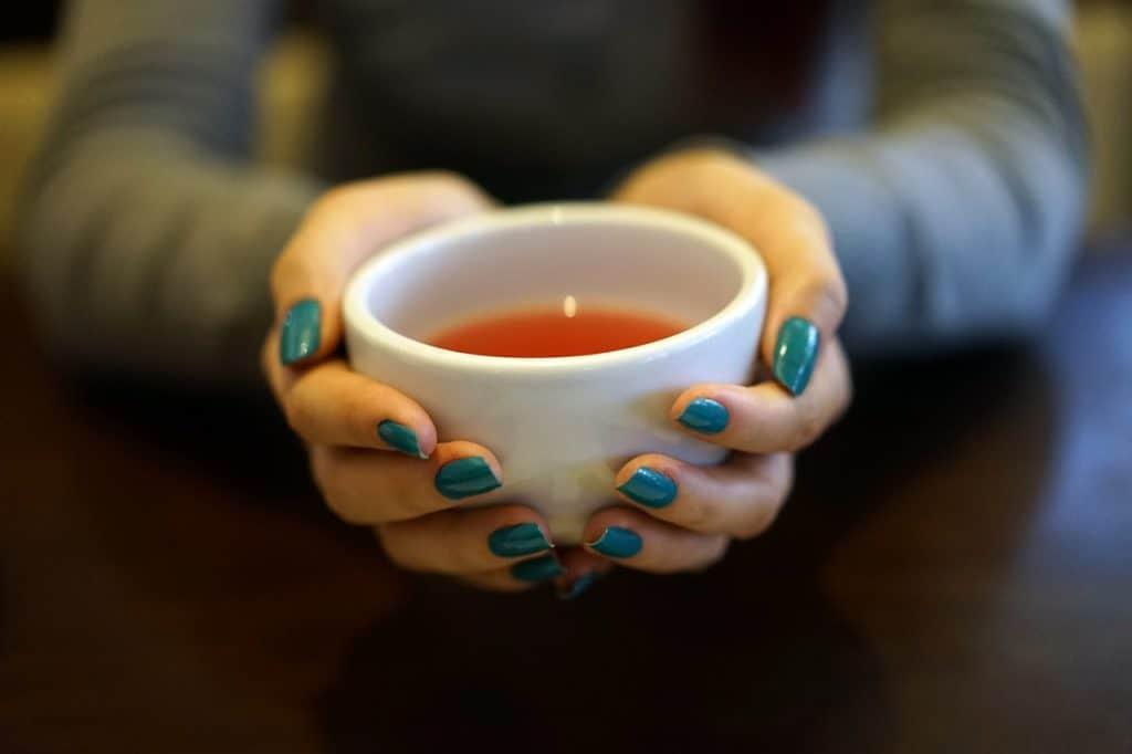Imagem de pessoa oferecendo xícara de chá sobre mesa de madeira.