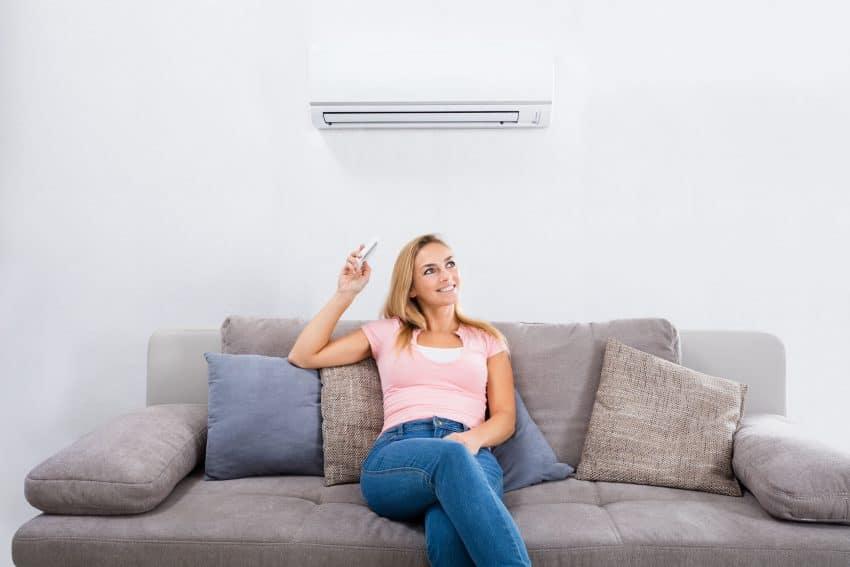 Mulher sentada em um sofá ligando o ar-condicionado e sorrindo.