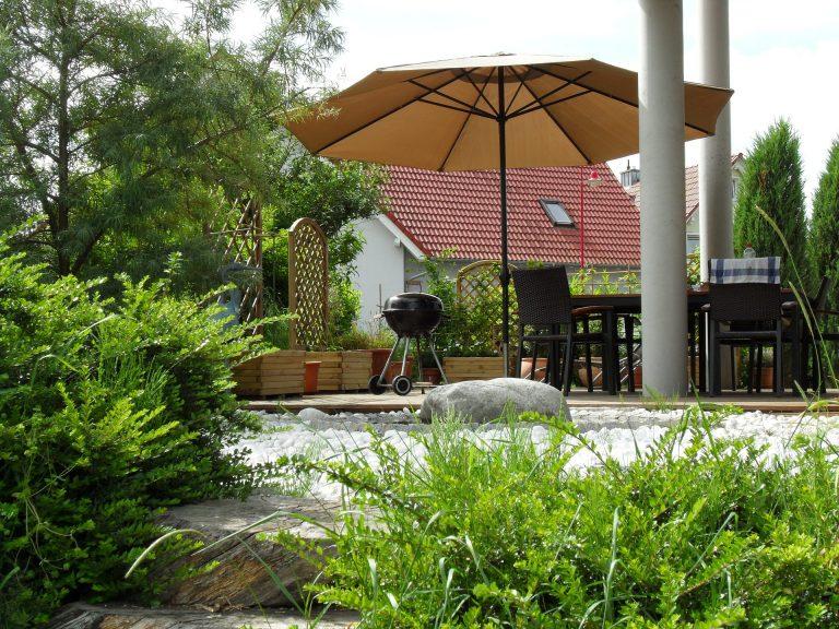 Conjunto para jardim com mesa, cadeiras e guarda sol usado próximo a churrasqueira