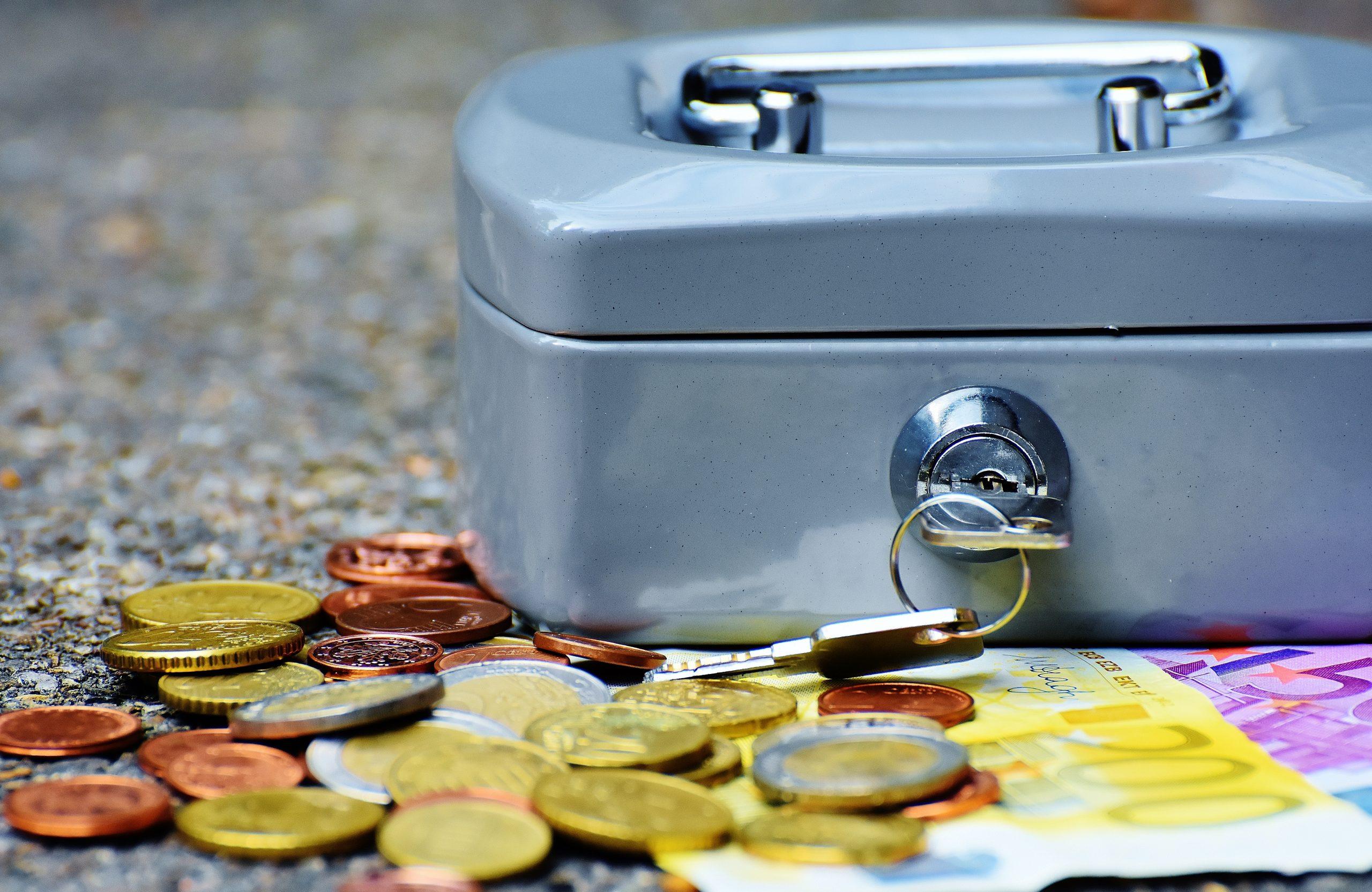 Imagem mostra um porta-valor fechado, com uma chave na fechadura. O cofre repousa sob uma superfície áspera e sob notas e moedas espalhadas.